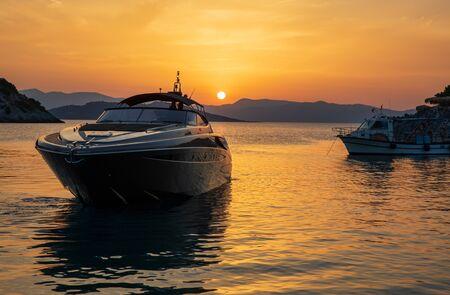 Yacht di lusso estivo al tramonto visto dalla spiaggia di Aponissos