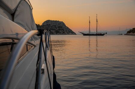 Summertime after sunset luxury yacht anchored in the Aponissos bay, Agistri island, Saronic gulf, Greece. Horizontal.