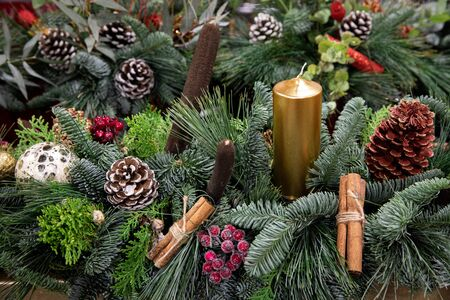 Beautiful arrangement from natural cones, red berries, cinnamon sticks, sprigs of pine, spruce, cypress and golden candle for festive interior decoration in the Christmas - New Year holidays.