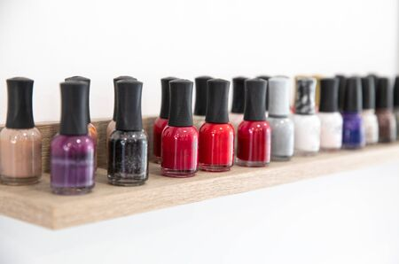 Nail polishes of different colors on shelf in the modern beauty salon isolated on white background. Horizontal. Selective focus. 版權商用圖片