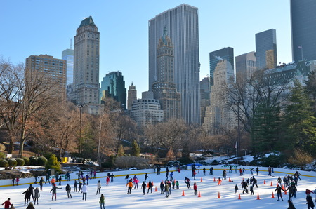 People skate on ice with white Christmas in Central Park, New York s famous Wollman Ice Rink