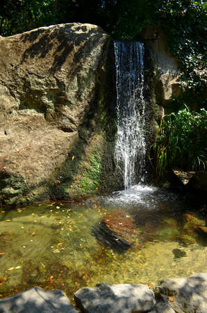 even: Small waterfall. Water flows on a block of stone and forms a small lake. The water that flows down from the mountains is very clean and clear, even see the sandy bottom in the form lakes.