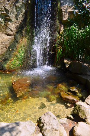 even: Small waterfall. Water flows on a block of stone and forms a small lake. The water that flows down from the mountains is very clean and clear, even see the sandy bottom in the form lakes