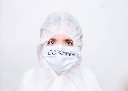 A virologist in a white mask and rubber gloves in a viral protective suit holds his head , looks fearfully at the camera and thinks about how to stop the coronavirus epidemic and what to do.