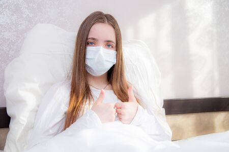 A young girl with dark hair in a white T-shirt lies in bed at home in a mask quarantine and looking at the camera with her hand showing the class that everything will be fine. the girl is recovering, recovering. Фото со стока