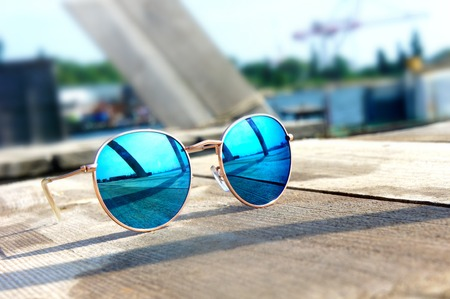 Fashionable mirror glasses with blue glasses on the sun lie on a wooden floor rest trip reflected in glasses Фото со стока
