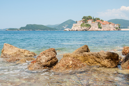 A view of the Sveti Stefan island and the mountains on a summer day, Montenegro, 2014 Stock Photo