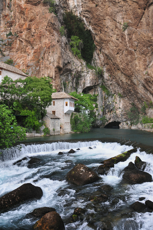 The Buna river with a waterfall flowing out of the cave, as well as the tekkia - an ancient dervish home, monks, Blagaj, Bosnia and Herzegovina