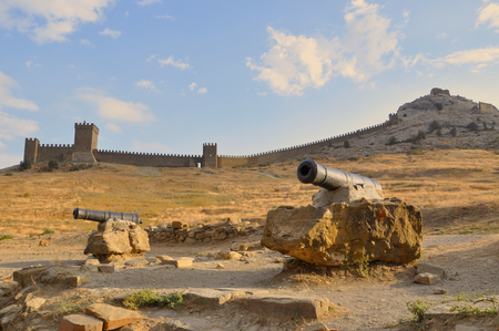 sudak: Ancient cannon in front of the old walls of the ancient Genoese fortress in Sudak, Crimea, Russia Stock Photo