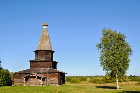 A wooden abandoned church near a birch tree in Veliky Novgorod on a summer evening, Russia. Stock Photo