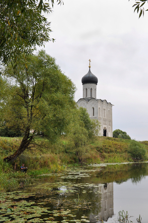 The boy is fishing for the Church of the Intercession on the Nerl with a UNESCO historical monument as part of the Golden Ring of Russia.