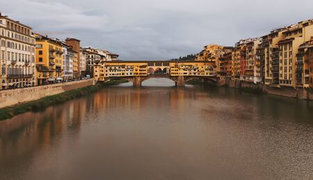 Moody day cityscape in Florence, Italy, bridge over Arno river.