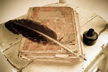 Old book, quill and black ink photo