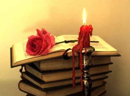 Oude boeken, rode roos en een kaars in sepia tone