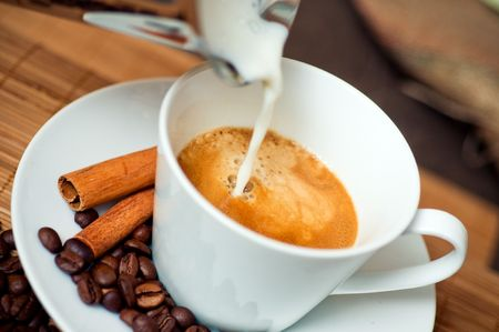 making coffee: Pouring milk into coffee Stock Photo