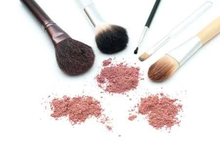 Makeup brushes and powder isolated on white