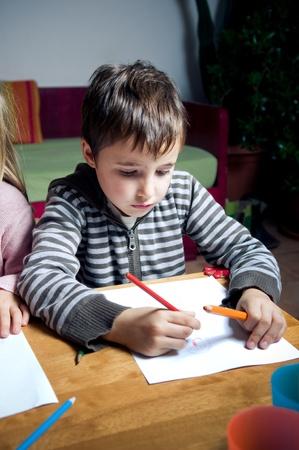 Kid dessin avec des crayons de couleur en bois