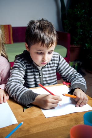 Kid zeichnen mit hölzernen Buntstifte
