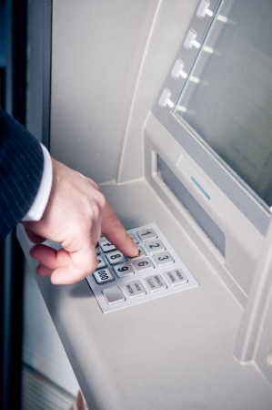 Hand entering personal identification number on ATM dial panel  photo