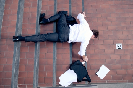 to stumble: Businessman falling down the stairs