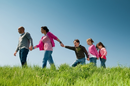Family walking outdoors holding hands