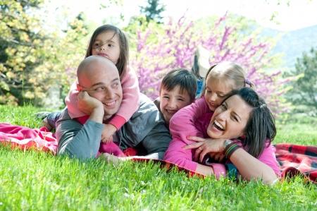 Famille heureuse sur une couverture dans la nature