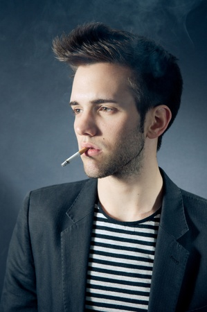 Cool young man smoking a cigarette photo