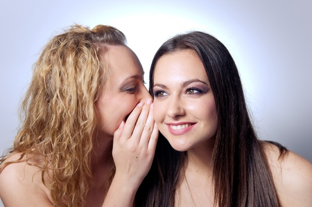 Young woman sharing secret to her friend  photo
