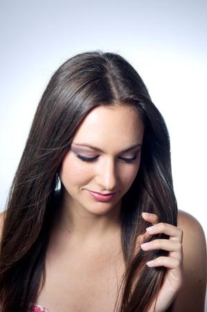 femme brune: Belle fille caucasienne tenant ses cheveux  Banque d'images