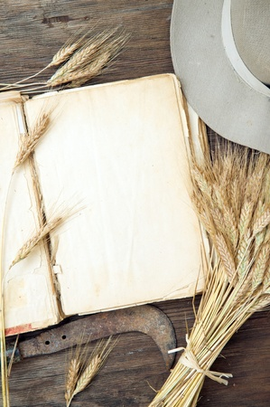 Old blank book on wooden background with wheat  photo