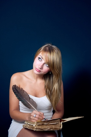 Beautiful girl writing with quill pen  photo