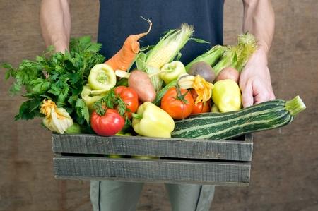 Détenant une caisse en bois avec des légumes frais