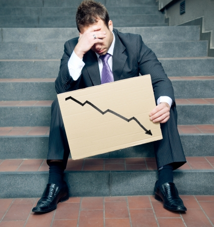 Desperate Businessman Showing Negative Graph photo