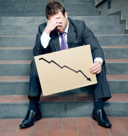 Verzweifelt Geschäftsmann zeigt Negativ Graph Standard-Bild