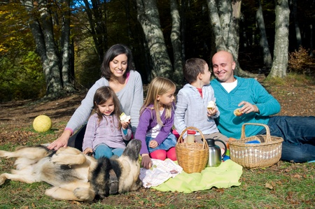 Happy family having picnic in autumn photo