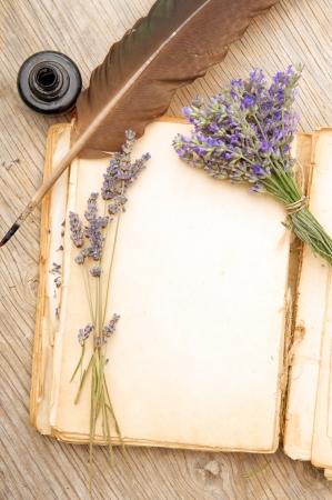 Geopend oud boek met lavendel bloemen op houten oppervlak Stockfoto