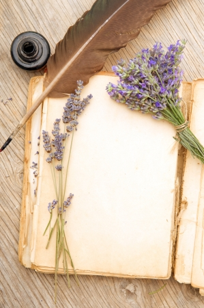 Opened old book with lavender flowers on wooden surface