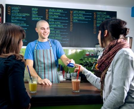 pagando: Bertender recibir la tarjeta de crédito del cliente para el pago en el café Foto de archivo