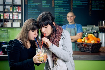 Two girls drinking smoothies with straws in cafe