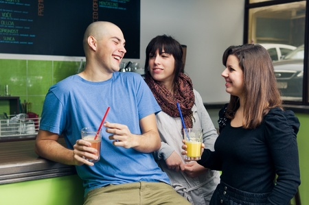 Three young friends having fun in cafe. Drinking smoothies.  photo