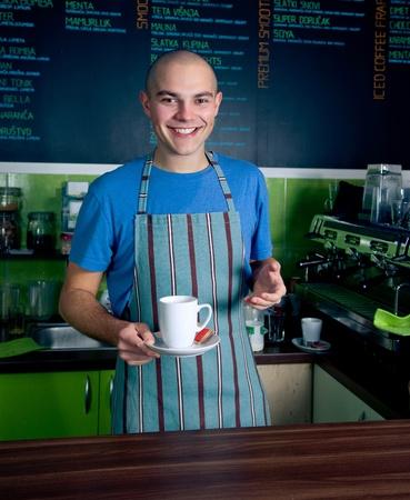 Jonge barman lachend en bedrijf kopje koffie.