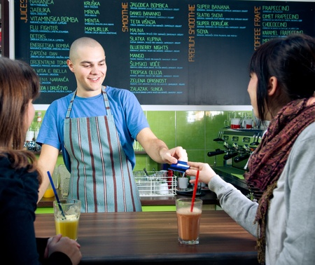 paying: Bartender receiving credit card of customer for payment in cafe Stock Photo