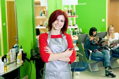 hair salon background: Happy hair salon owner or employee with customers in the background