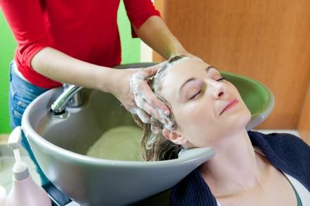 Woman washing hair in hair salon photo