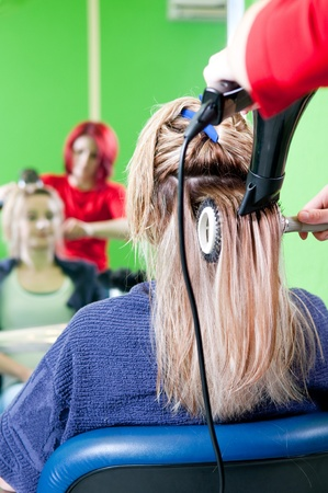 Close up of girl head in beauty salon while an hair stylist brush and dry her hair photo