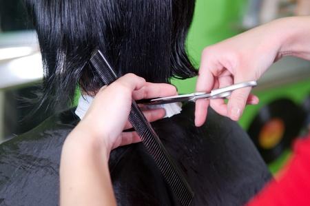 horizontal haircut: Cutting dark hair close-up, hair salon
