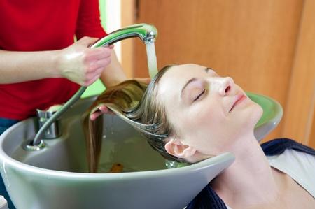 Femme se laver les cheveux dans un salon de coiffure