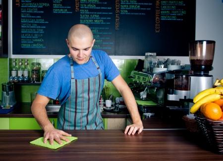 číšník: Mladý barman čištění desku s houbou Reklamní fotografie