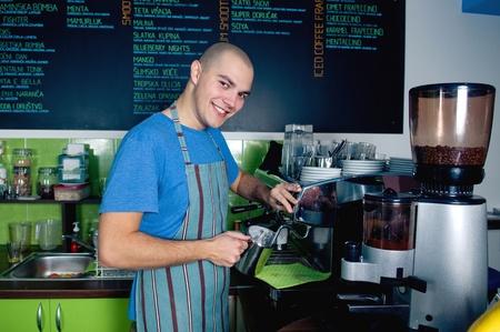 Jeune barman souriant et en faisant tasse de café. Banque d'images