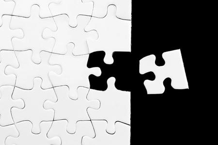 Lege witte puzzel met ontbrekende stuk. Zwarte achtergrond. Stockfoto